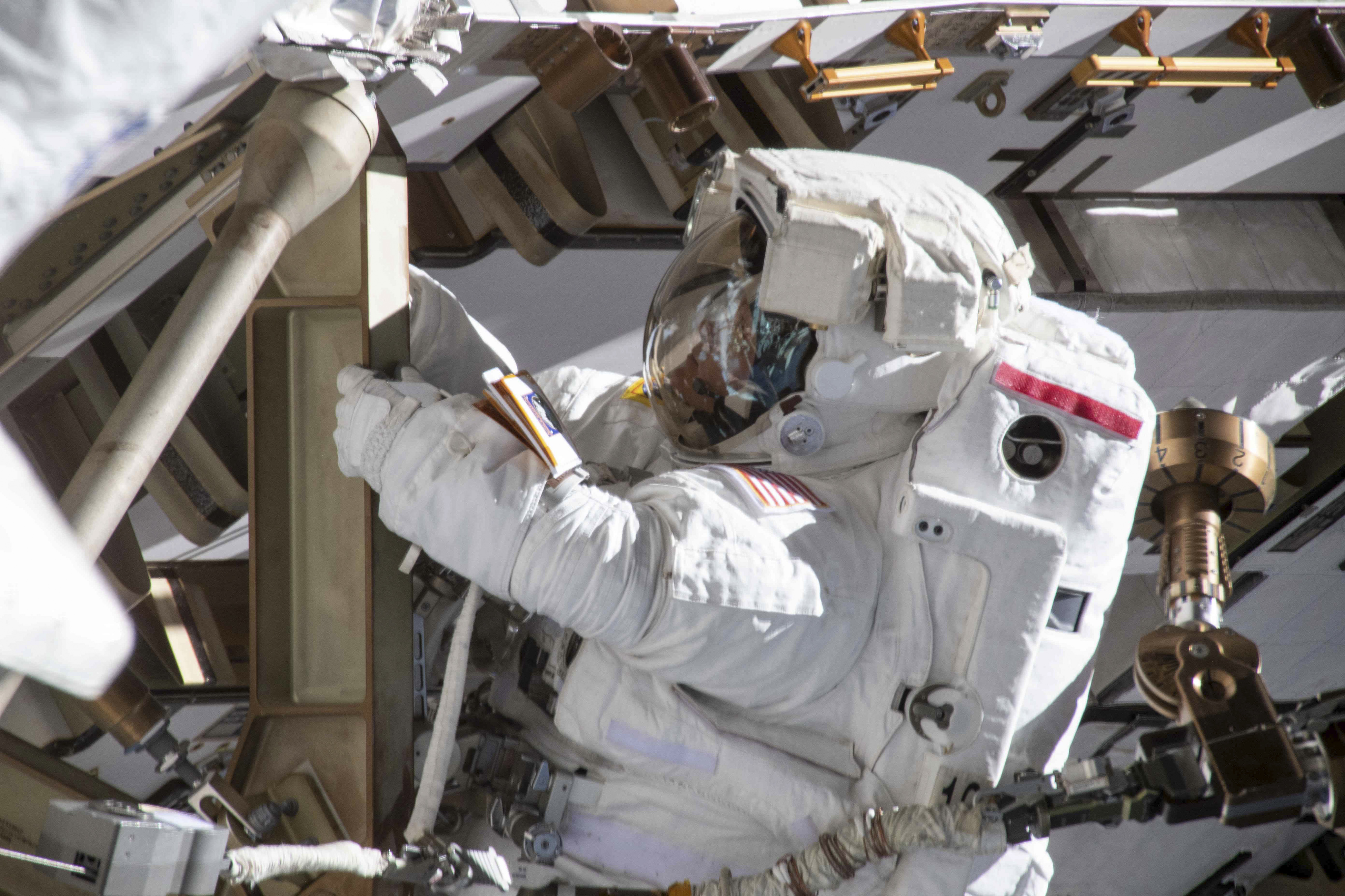 A photo provided by NASA of Anne McClain working on the International Space Station's Port-4 truss structure during a 6-hour 39-minute spacewalk to upgrade the station's power storage capacity.