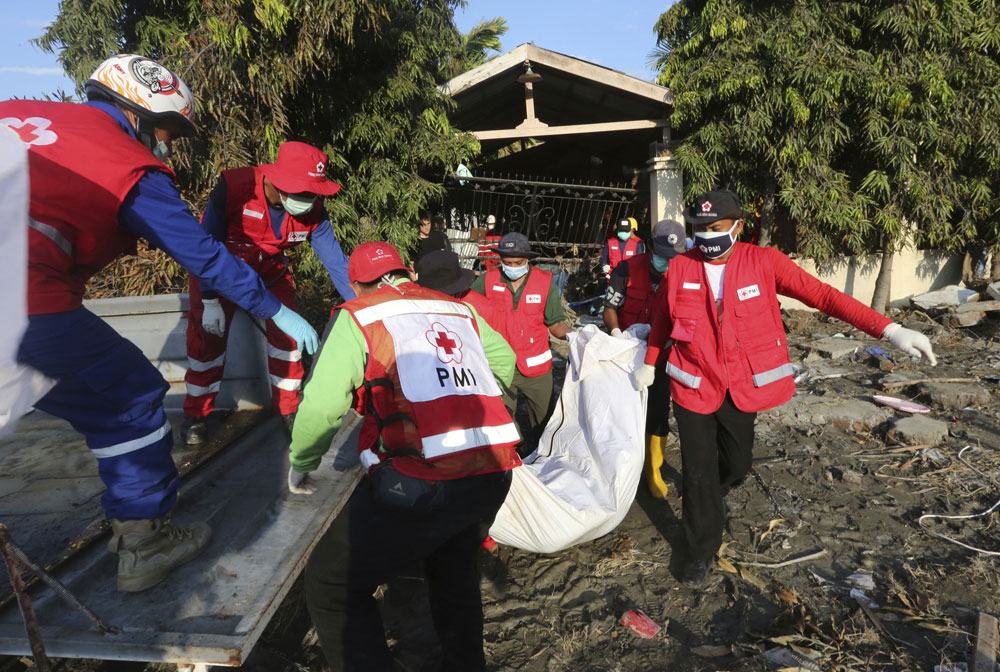 Indonesian red cross team carry the body of a tsunami victim in Palu