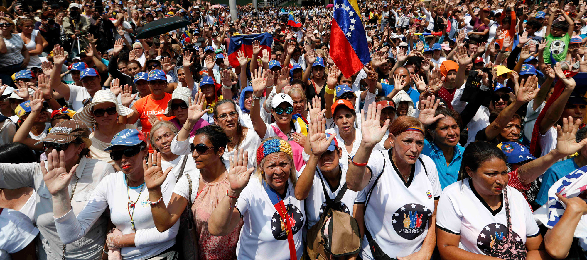 Venezuelan women take an oath to fight for women's rights during a rally to commemorate International Women's Day in Caracas, Venezuela on Friday, March 8, 2019.