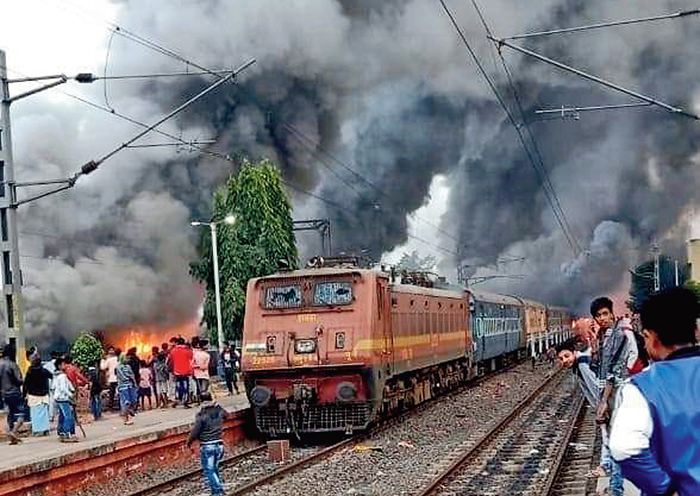 Smoke billows out of coaches set ablaze by the protesters at Krishnapur railway station in Murshidabad