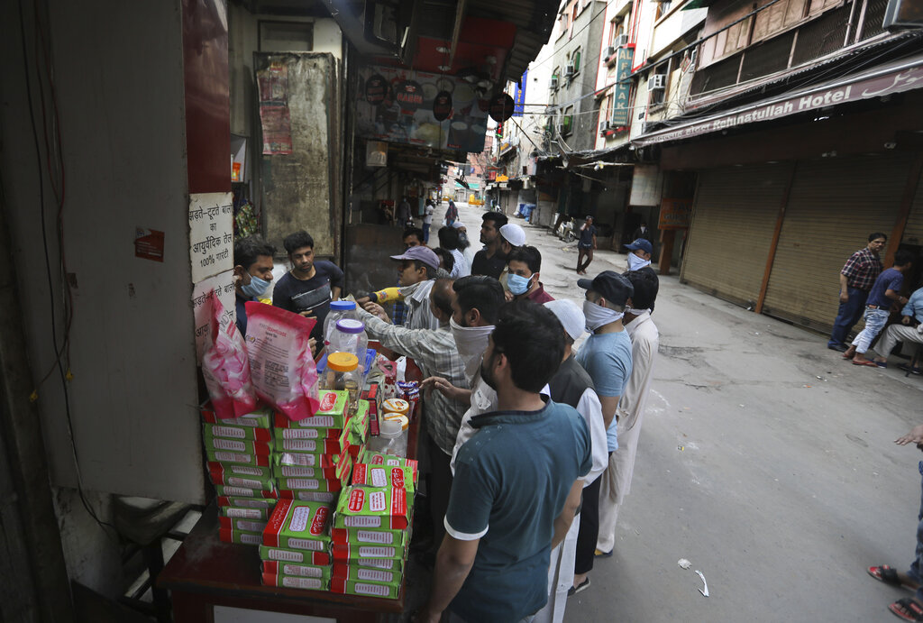 People buy groceries during a lockdown to control the new virus spread, in New Delhi, on Wednesday, March 25, 2020