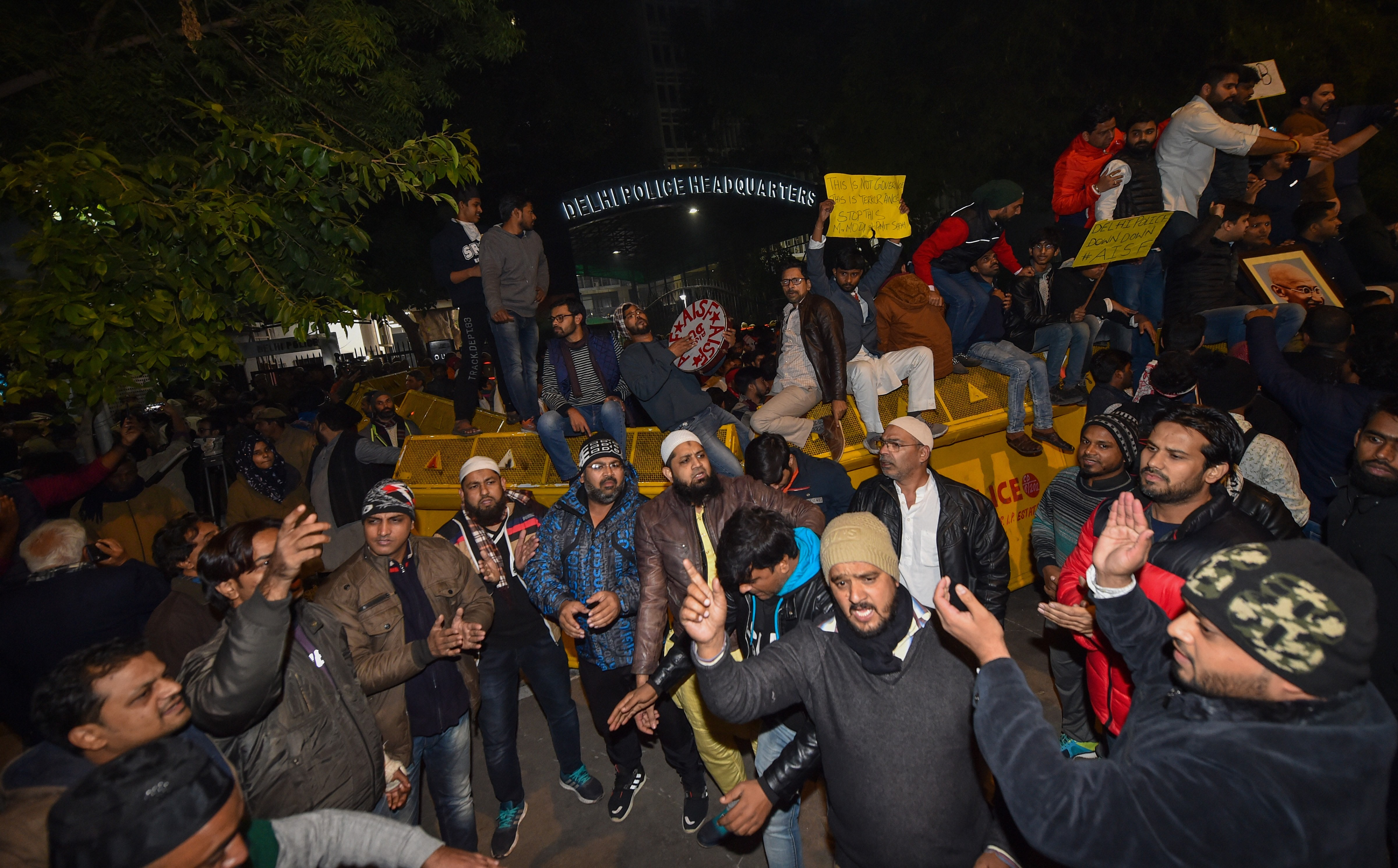 Students and others protest the police action against the students of the Jamia Millia Islamia University at police headquarters in New Delhi, Sunday night, December 15, 2019