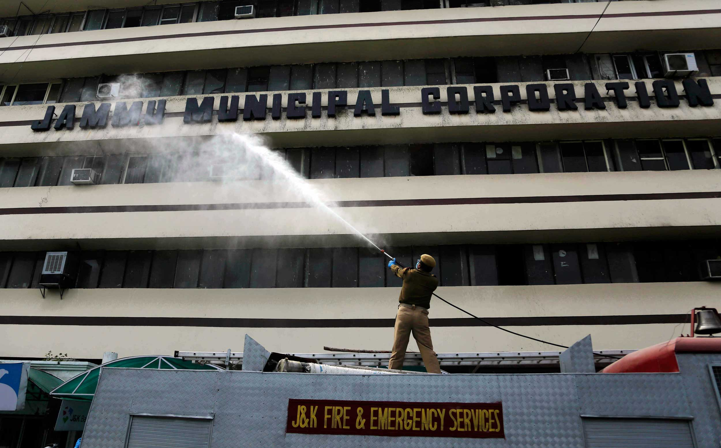 A firefighter disinfects the JMC building during the lockdown in Jammu on Tuesday.