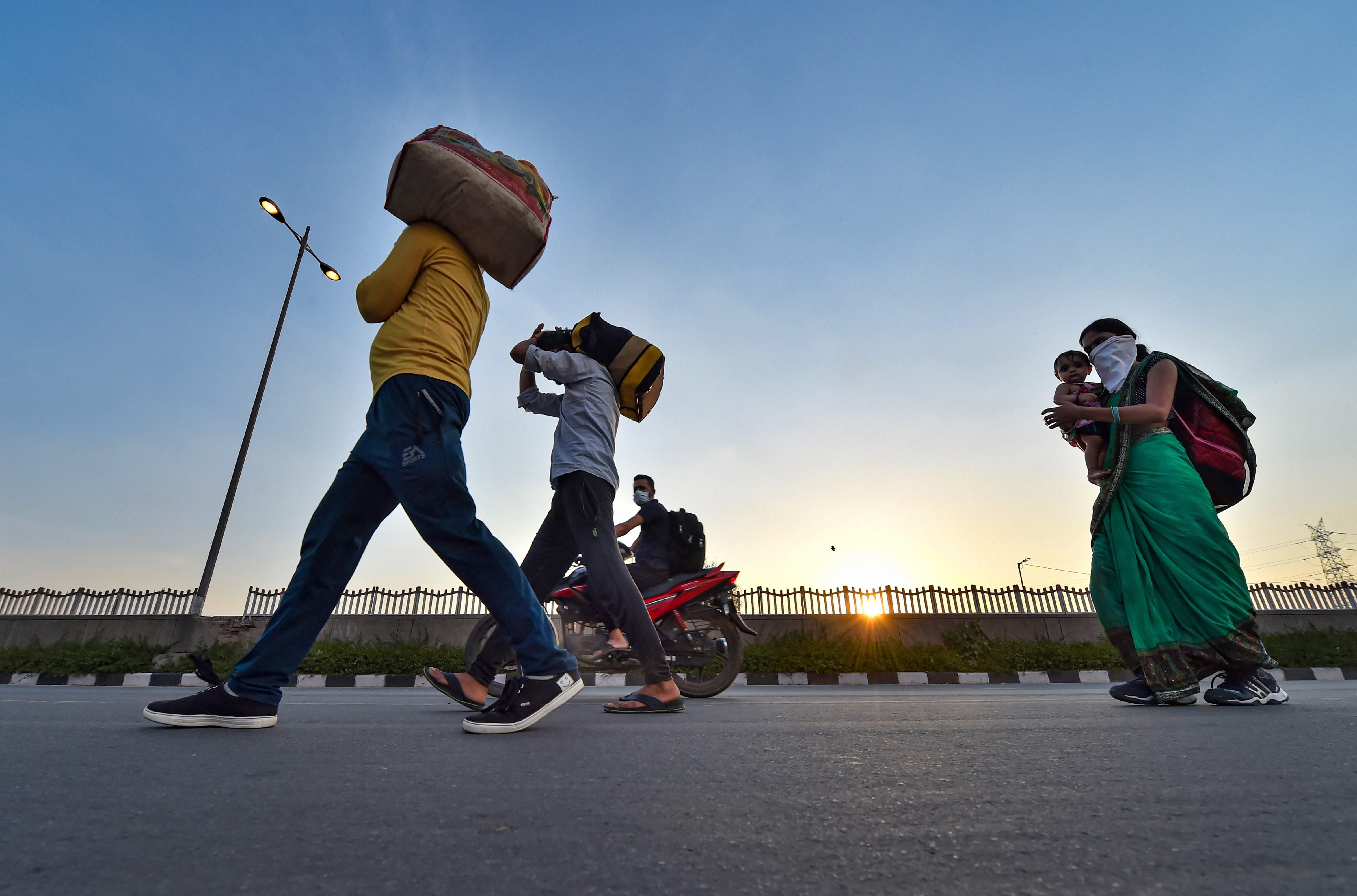 Migrant workers along with their family members walk along the Delhi-UP border road during the ongoing Covid-19 nationwide lockdown, in East Delhi, Tuesday, May 5, 2020.