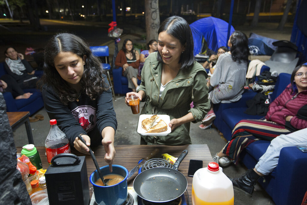 In this February 24, 2020 photo, Ximena, 19, left, and Melani, 20, prepare food for fellow students during an indefinite take-over of the School of Political and Social Sciences of the National Autonomous University of Mexico, or UNAM, in Mexico City. Since October, the students have forcibly occupied several schools and faculties to demand security and greater punishment for acts of gender violence.
