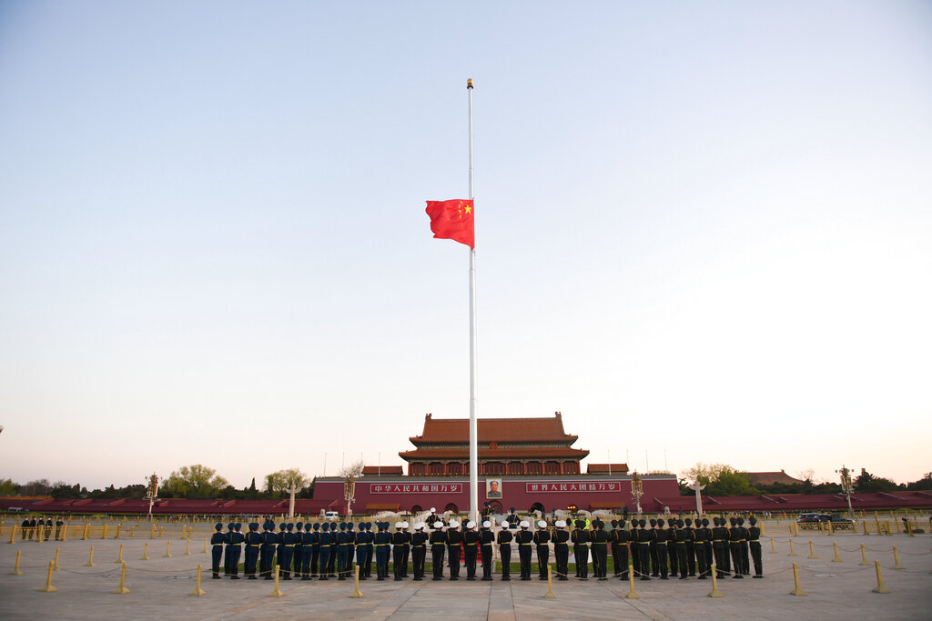 In this photo released by China's Xinhua News Agency, an honor guard stands in formation as a Chinese national flag flies at half-staff at Tiananmen Square in Beijing, Saturday, April 4, 2020.