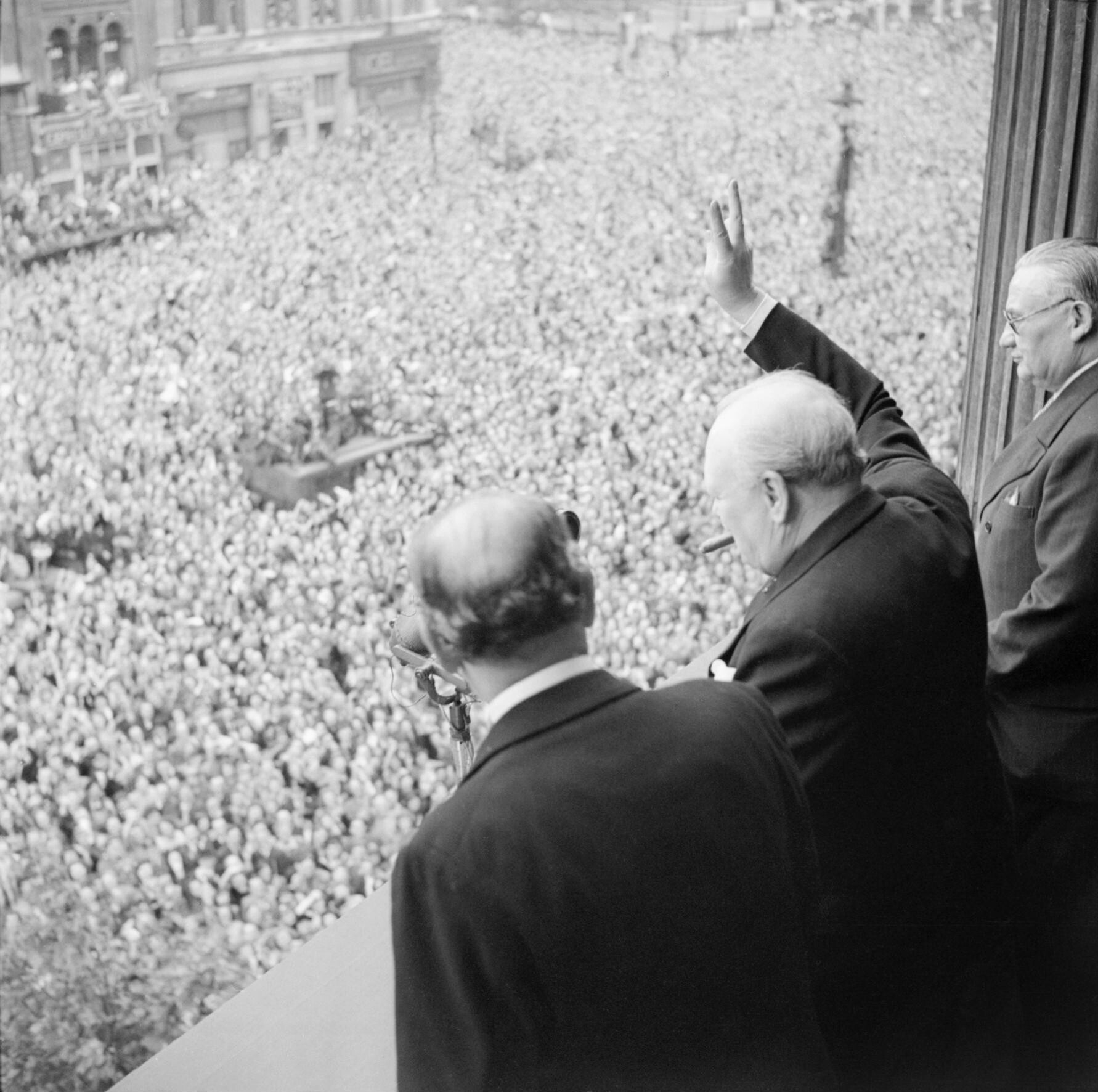 Churchill waves to the crowds in London as they celebrate VE Day