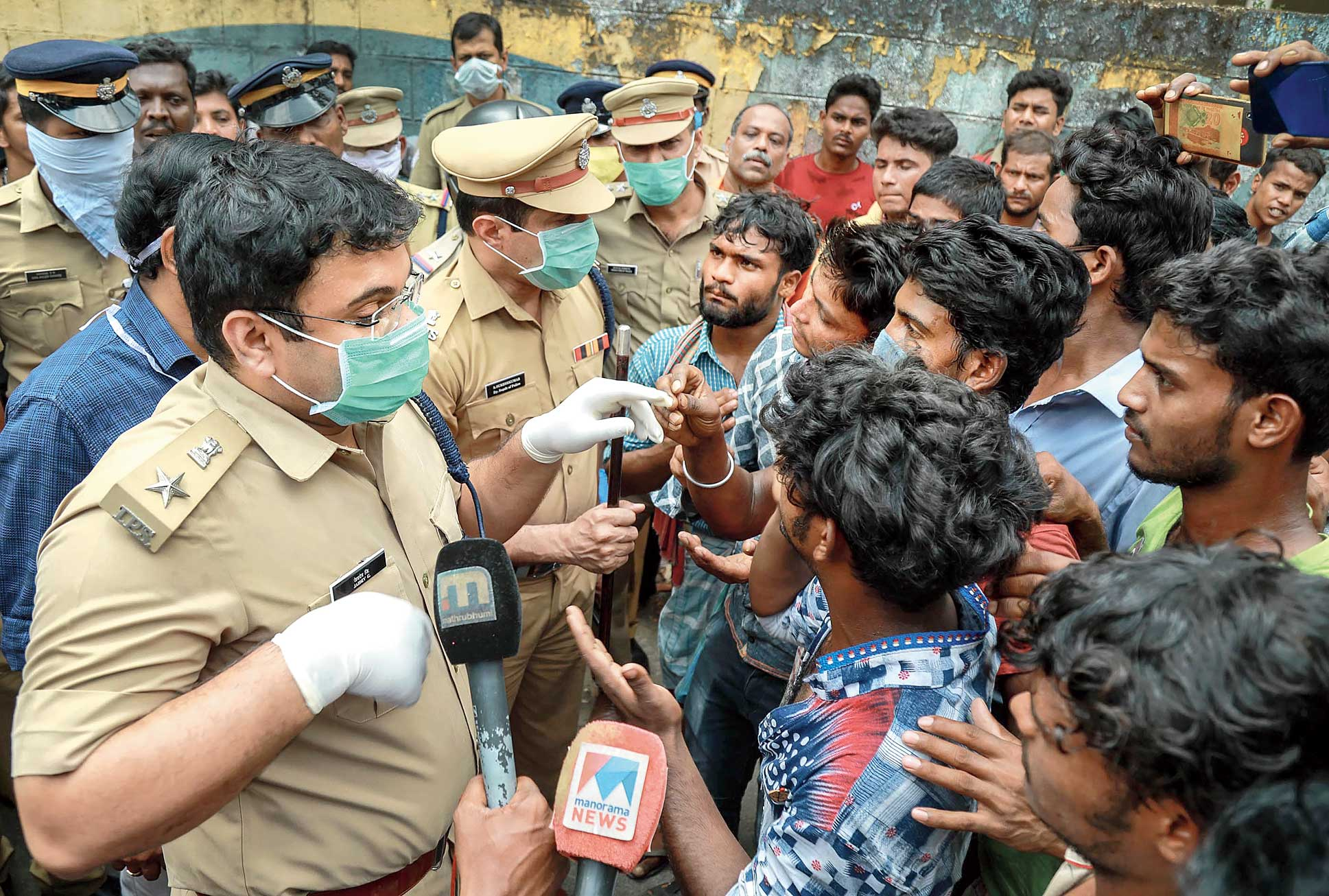 Policemen speak to the agitating migrants from Bengal in Kottayam, Kerala, on Sunday.