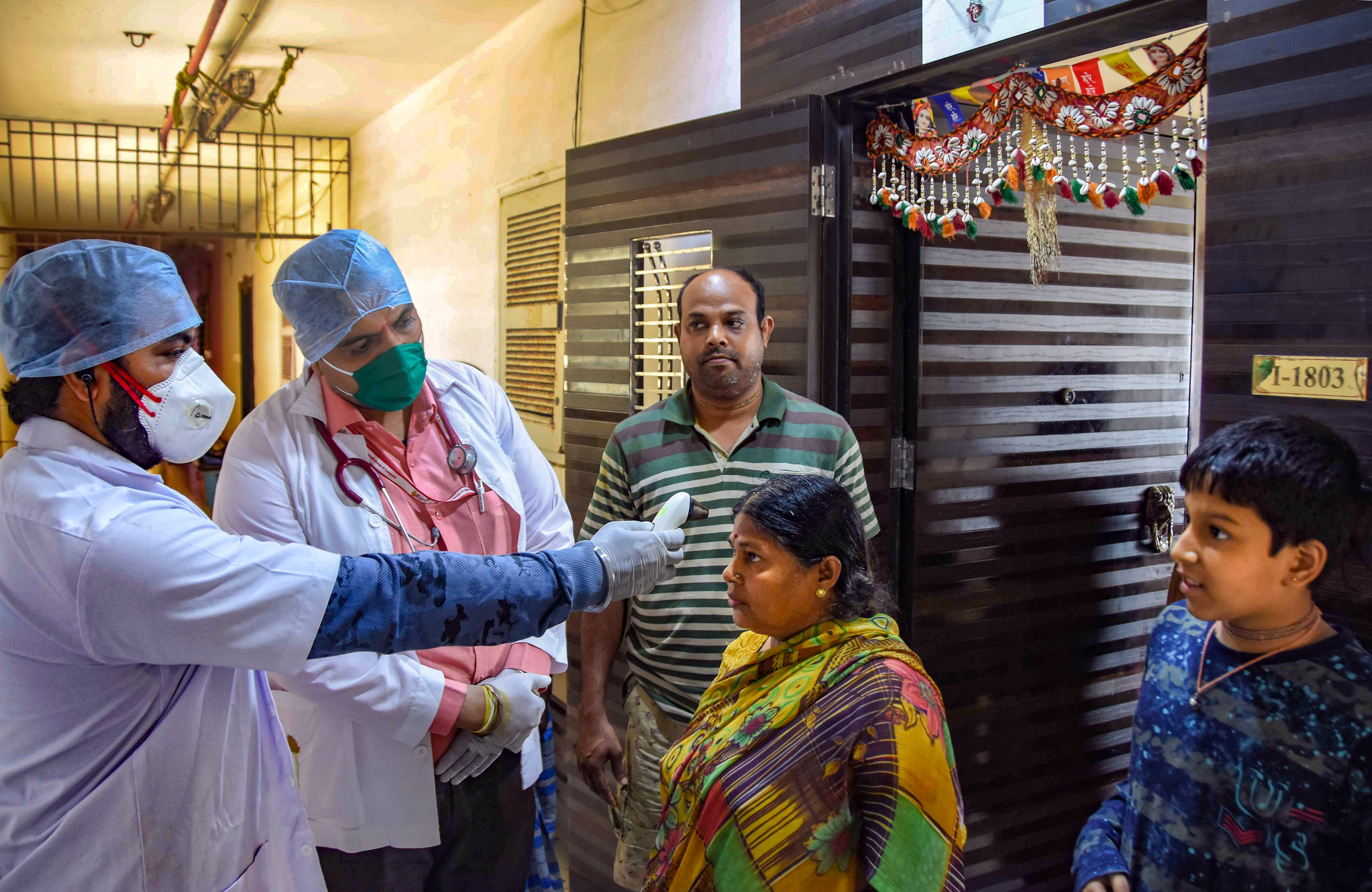 Medics from Rs 1 clinic conduct a door-to-door thermal screening of residents, during a nationwide lockdown, imposed in the wake of coronavirus pandemic, in Mumbai, Sunday, March 29, 2020