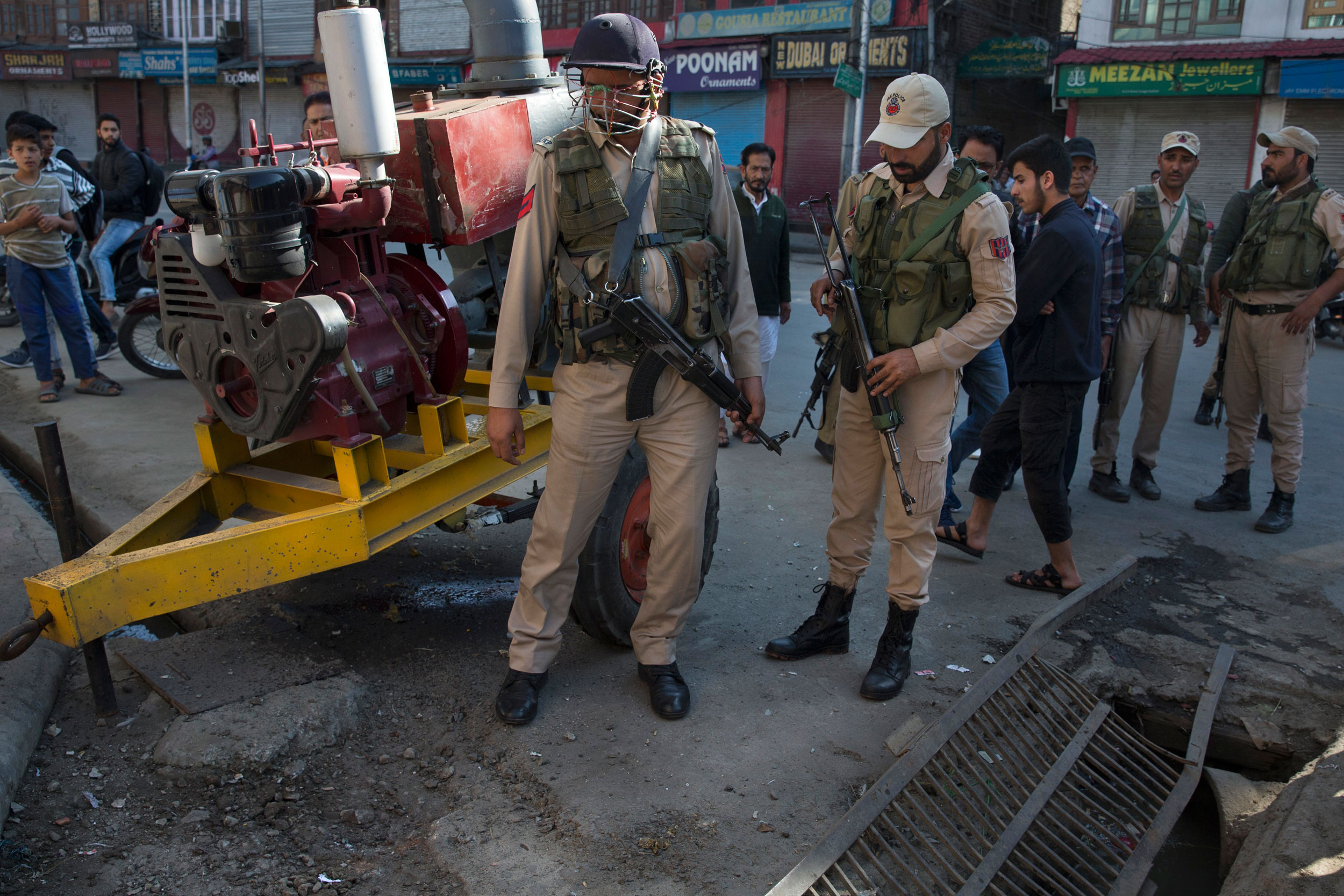 Police officers at the site of a grenade attack in Srinagar on Saturday.
