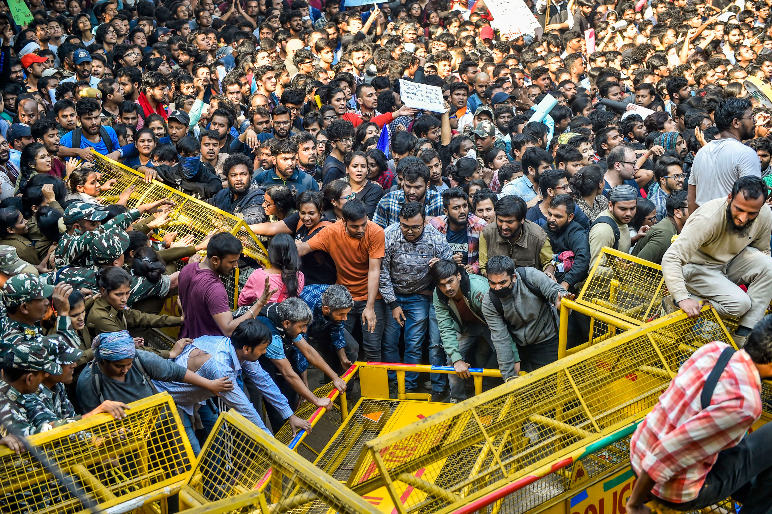 JNU students try to get past police barricades during a protest march in New Delhi on November 18, 2019.