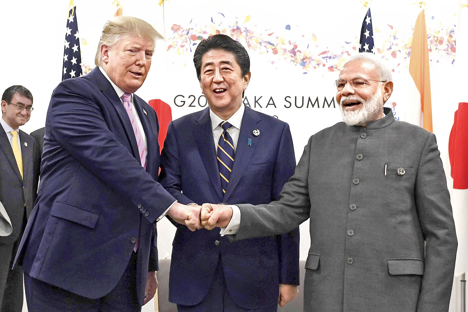 Donald Trump (left) does a fist bump with Shinzo Abe (centre) and Narendra Modi in Osaka on Friday.