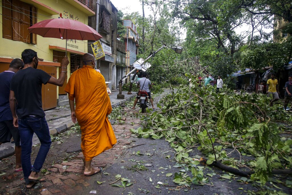 A Buddhist monk walks through a road laid with fallen trees and branches after cyclone Amphan hit the region in Calcutta, Thursday, May 21, 2020.
