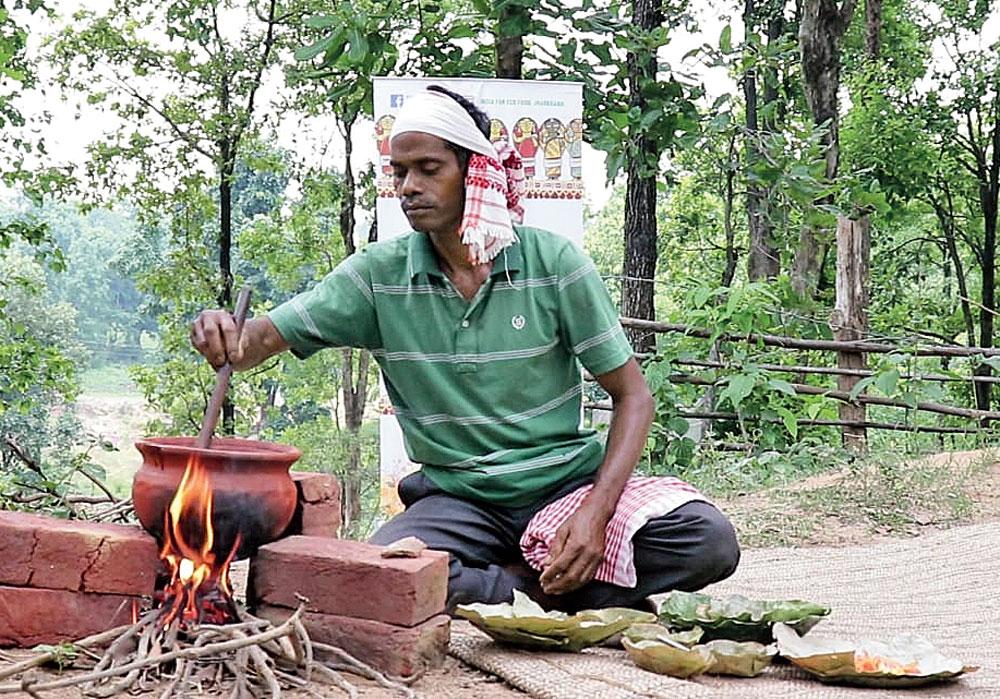 Farmer Anil Kujur prepares a tribal delicacy.