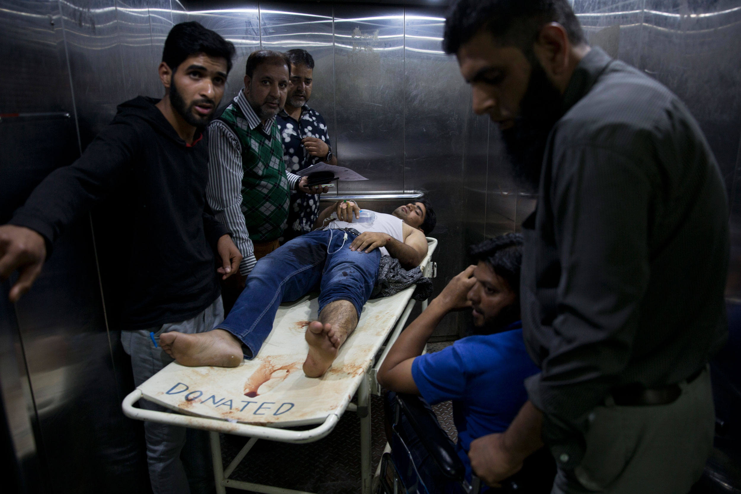 Kashmiris accompany a wounded man for treatment after an explosion in Srinagar on October 12, 2019.