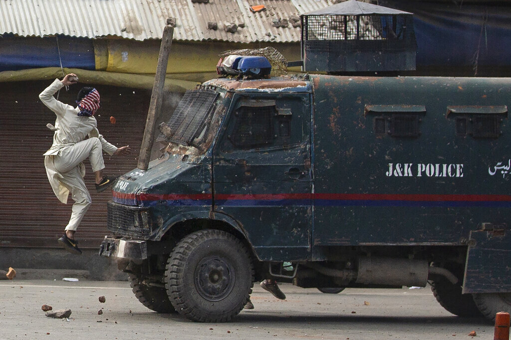 A masked Kashmiri protester jumps on the bonnet of an armored vehicle of Indian police as he throws stones at it during a protest in Srinagar, May 31, 2019. The image was part of the series, which won the 2020 Pulitzer Prize for Feature Photography.