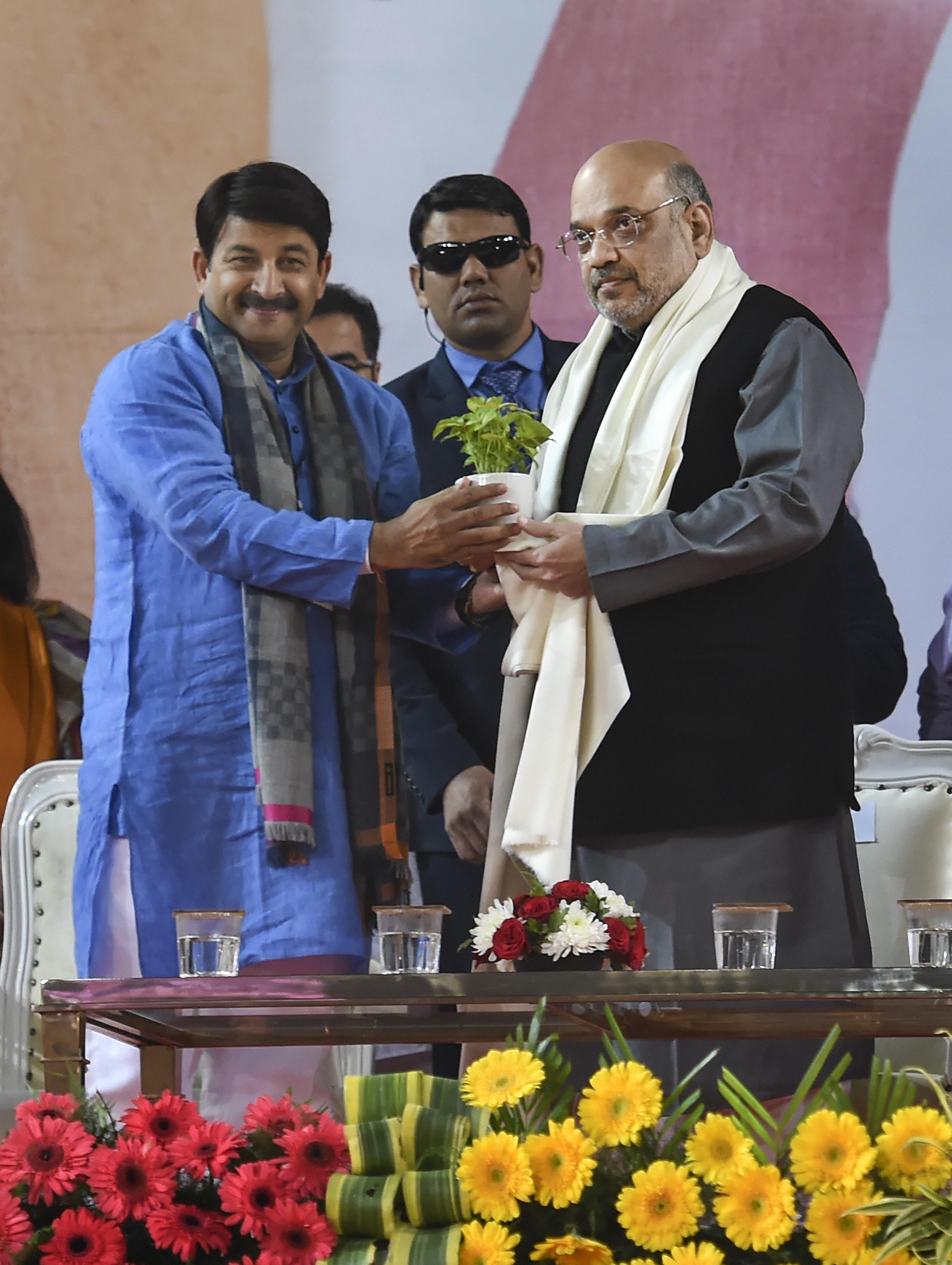Union home minister Amit Shah being presented a sapling by Delhi BJP president Manoj Tiwari during BJP's booth-level workers' rally 'Delhi Karyakarta Samelan' in New Delhi, Sunday, January 5, 2020.