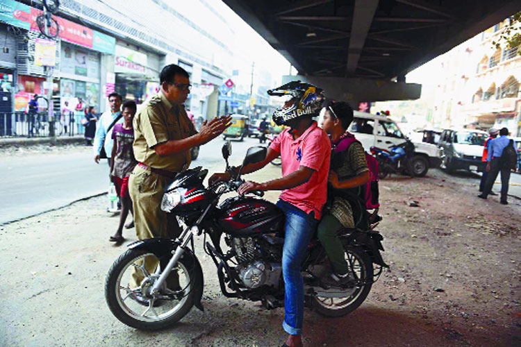 A police officer requests a man to follow traffic rules after spotting the pillion rider without a helmet near the Nagerbazar crossing on Friday.