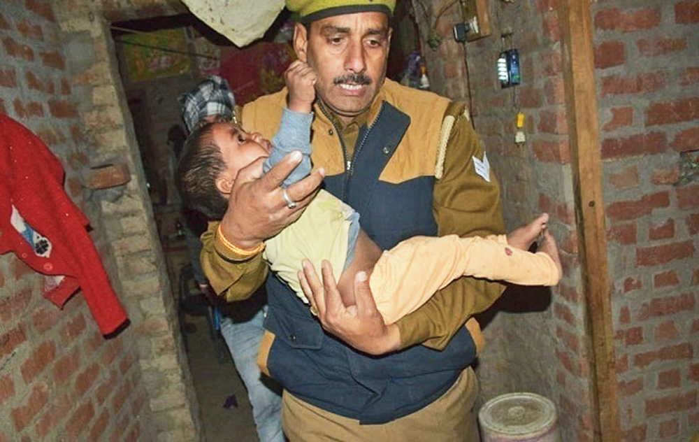 A policeman carries a child out of the house in Uttar Pradesh's Farrukhabad on Thursday
