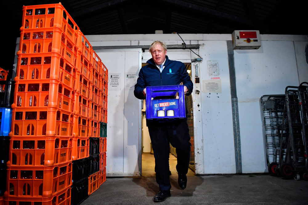 Boris Johnson in Leeds on December 11 carries a crate of milk bearing the Conservative Party campaign slogan on the last day of campaigning ahead of Thursday's general election