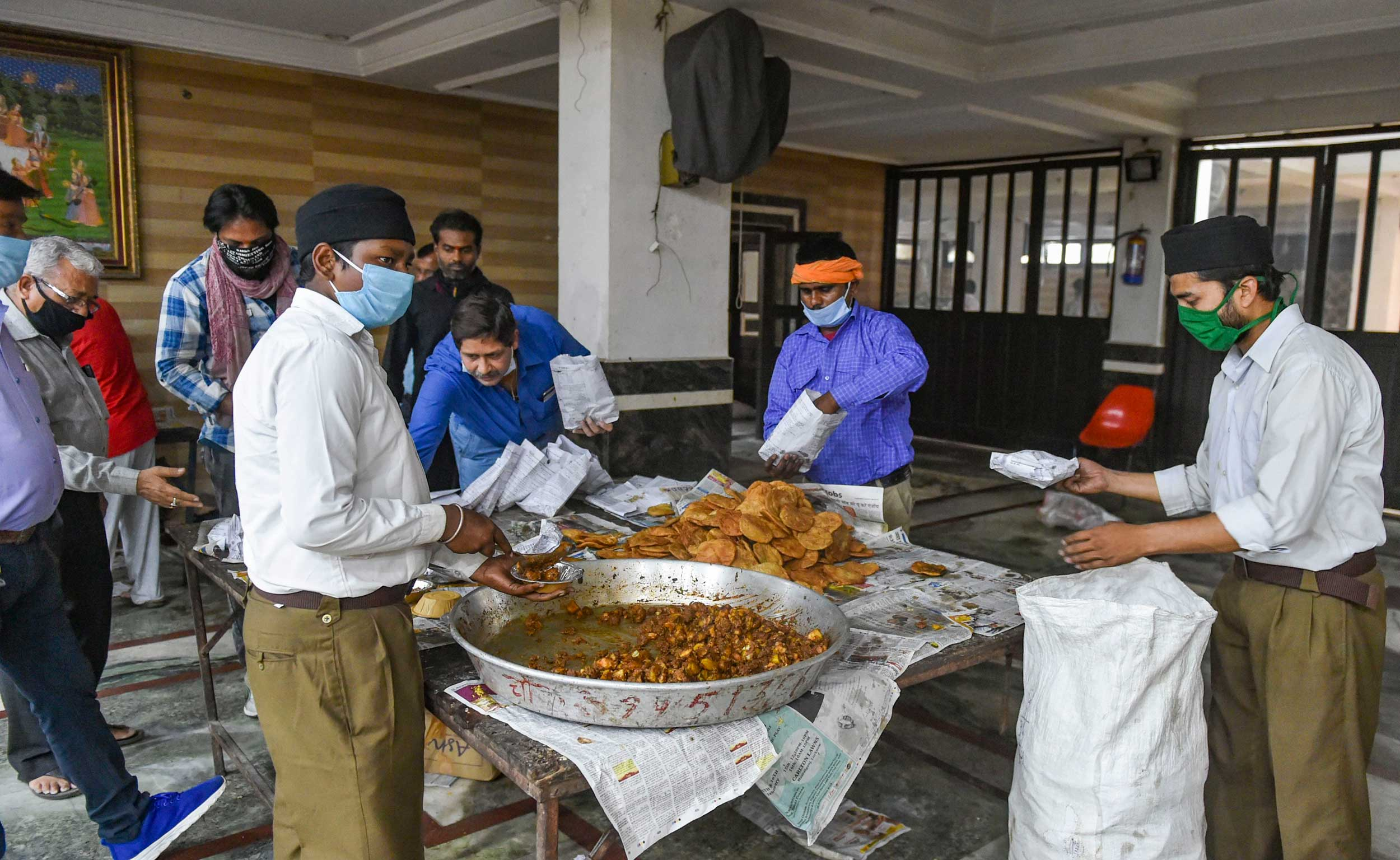 Volunteers pack food for the needy during the nationwide lockdown in Lucknow on Friday.