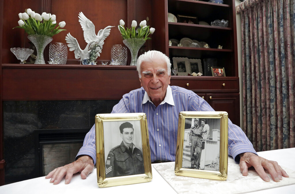 In this photo taken May 20, 2019, veteran Norman Harold Kirby sits with a photo of his mother, Katherine Louise Kirby, and himself, at 17, and a post-war portrait as he poses for a photo at his home in Lions Bay, Canada. The Canadian from British Columbia had joined the army when he was only 17 and was barely a 19-year-old private when he climbed into the landing craft that would take him to shore on June 6, 1944.
