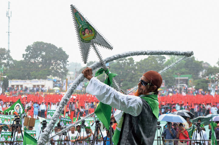 A JMM supporter holds a bow and arrow, the party's poll symbol, at the Badlav rally on Harmu ground in Ranchi on Saturday