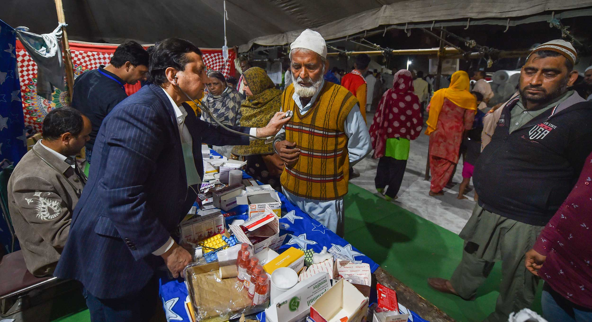 Members of Doctors Unity Welfare Association distribute medicines to people affected in the riots at eidgah relief camp in Mustafabad on Tuesday.