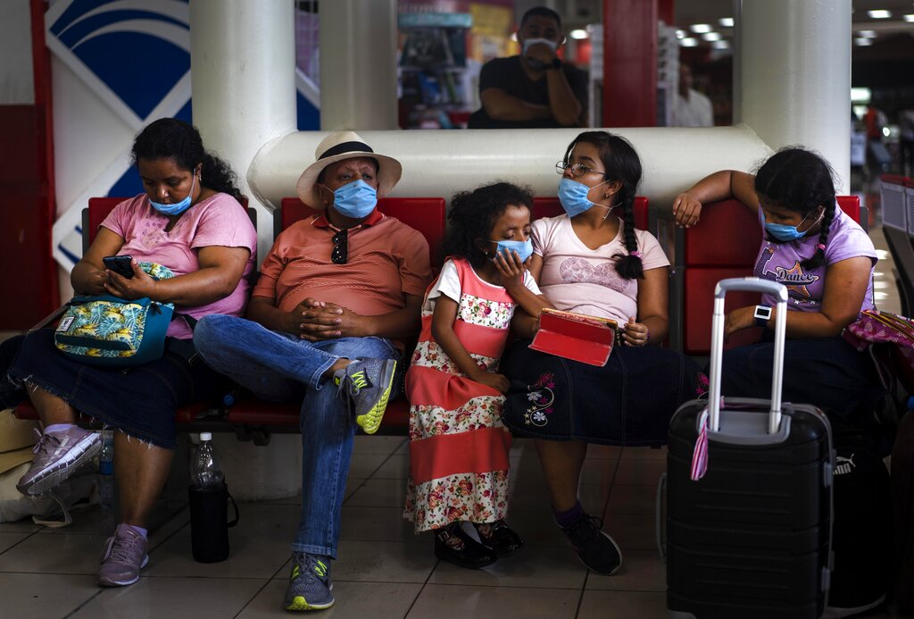 Tourists from Mexico wearing masks as a precaution against the spread of the new coronavirus, wait for their flight home, at the Jose Marti International Airport in Havana, Cuba, Monday, March 23, 2020. The vast majority of people recover from the COVID-19 disease.