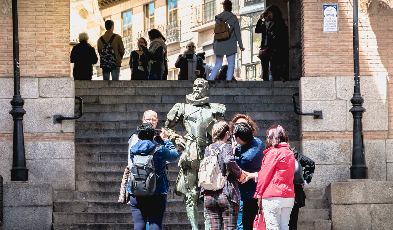 Tourists taking pictures of the Statue of Miguel de Cervantes near the main square of Toledo, Spain