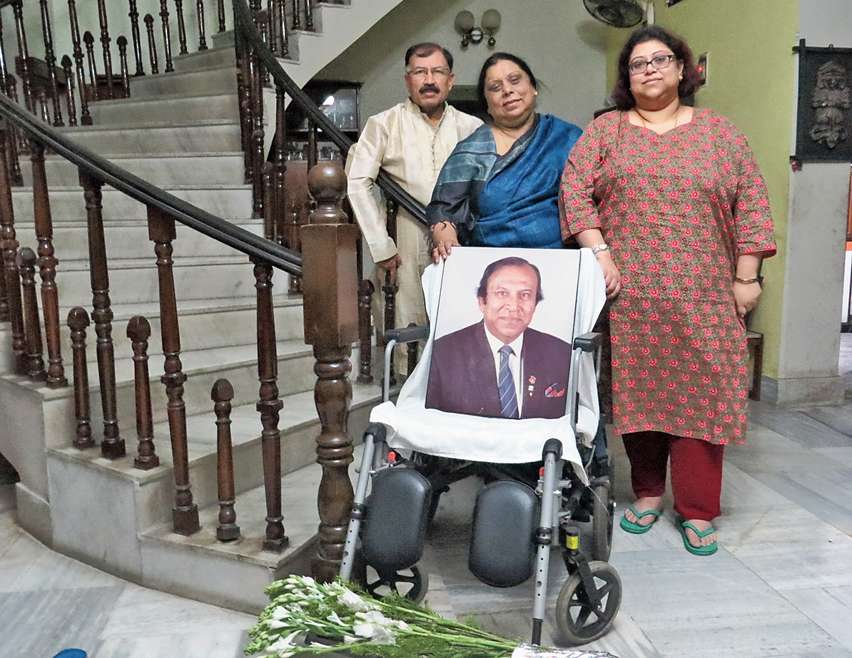 Brother Prasun and daughters Paula and Purna with the wheelchair where PK Banerjee would sit in his drawing room.