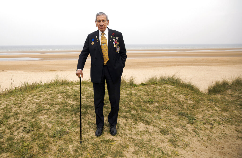 World War II and D-Day veteran Charles Norman Shay, from Indian Island, Maine, poses on a dune at Omaha Beach in Saint-Laurent-sur-Mer, Normandy. Shay was a combat medic on D-Day, assigned to an assault battalion in the first wave of attacks on D-Day, June 6, 1944.