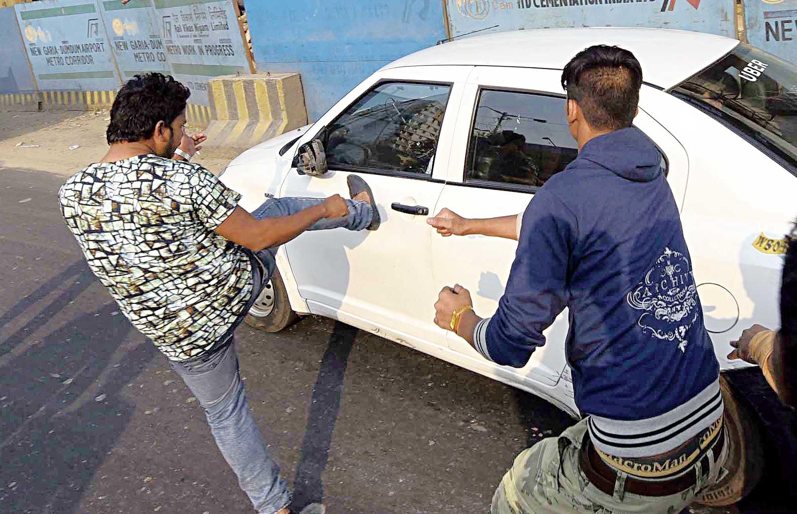 A protester kicks the door of an app cab on EM Bypass on December 27