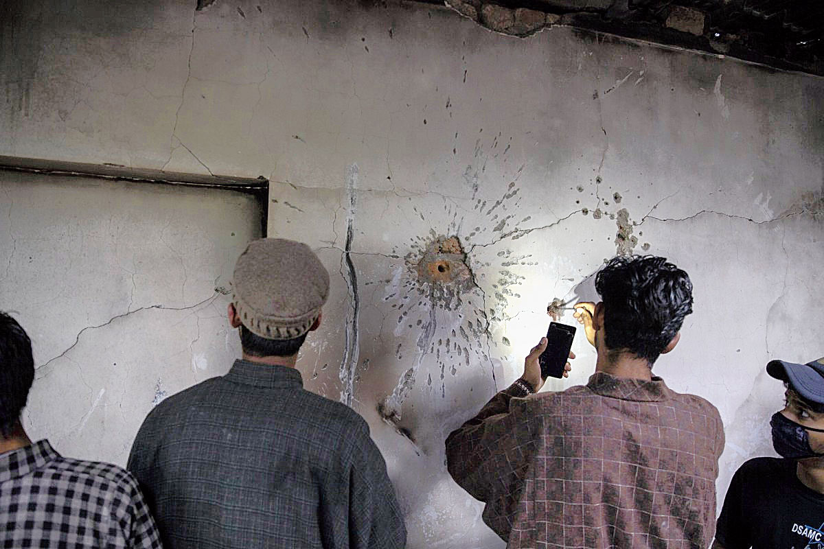 A Kashmiri boy tries to take out a bullet from the wall of a damaged house after a gun battle in Tral, south of Srinagar, on May 24, 2019.