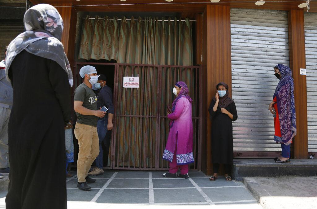 Kashmiris wearing masks wait outside a bakery ahead of Eid al-Fitr during a nationwide lockdown to control the spread of coronavirus, in Srinagar, Wednesday, May 20, 2020.
