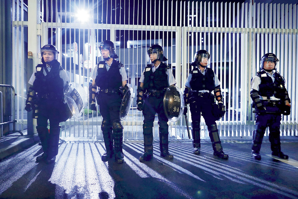 Policemen in anti-riot gear stand guard outside the Legislative Council in Hong Kong on Tuesday