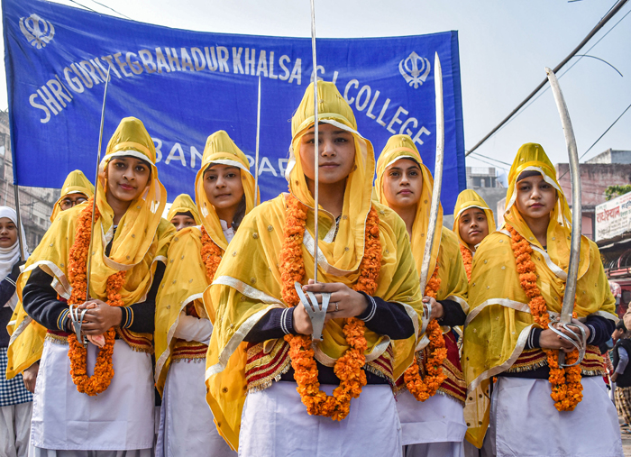 Girls dressed as Panj Pyaras participate in a procession ahead of the birth anniversary of Guru Gobind Singh Ji, in Prayagraj