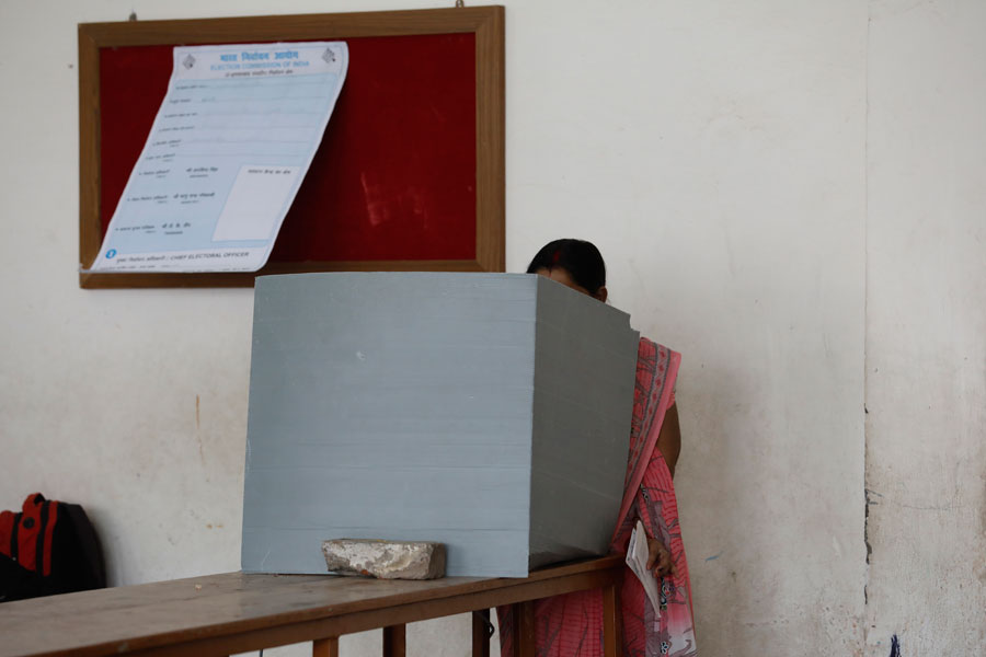 A woman casts her vote inside a polling station in Allahabad, Uttar Pradesh on Sunday, May 12, 2019.