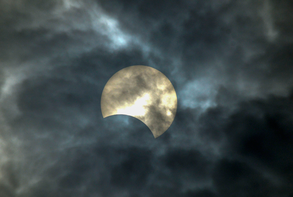 A view of the solar eclipse as seen in the cloudy sky from Karad, Maharashtra, on December 26