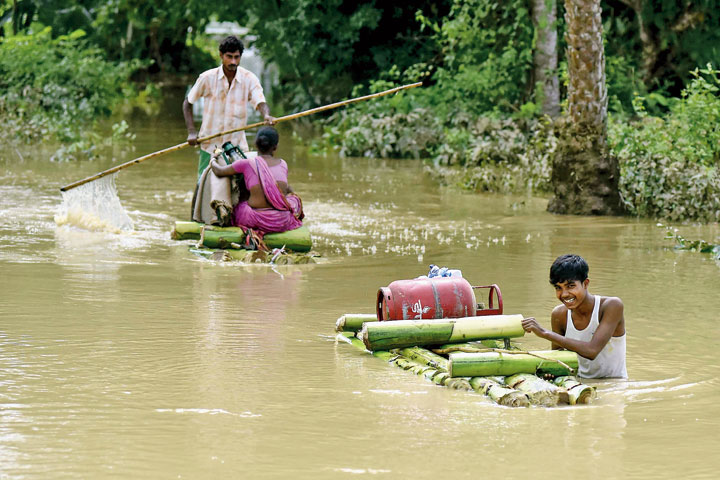 Villagers wade through floodwaters on a rafts as they carry their belongings to a safer place in Nagaon district of Assam  on Monday