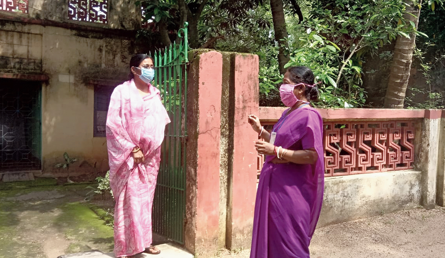 Asha worker Mithu Singha (right) making door-to-door enquiries whether anyone has fever.