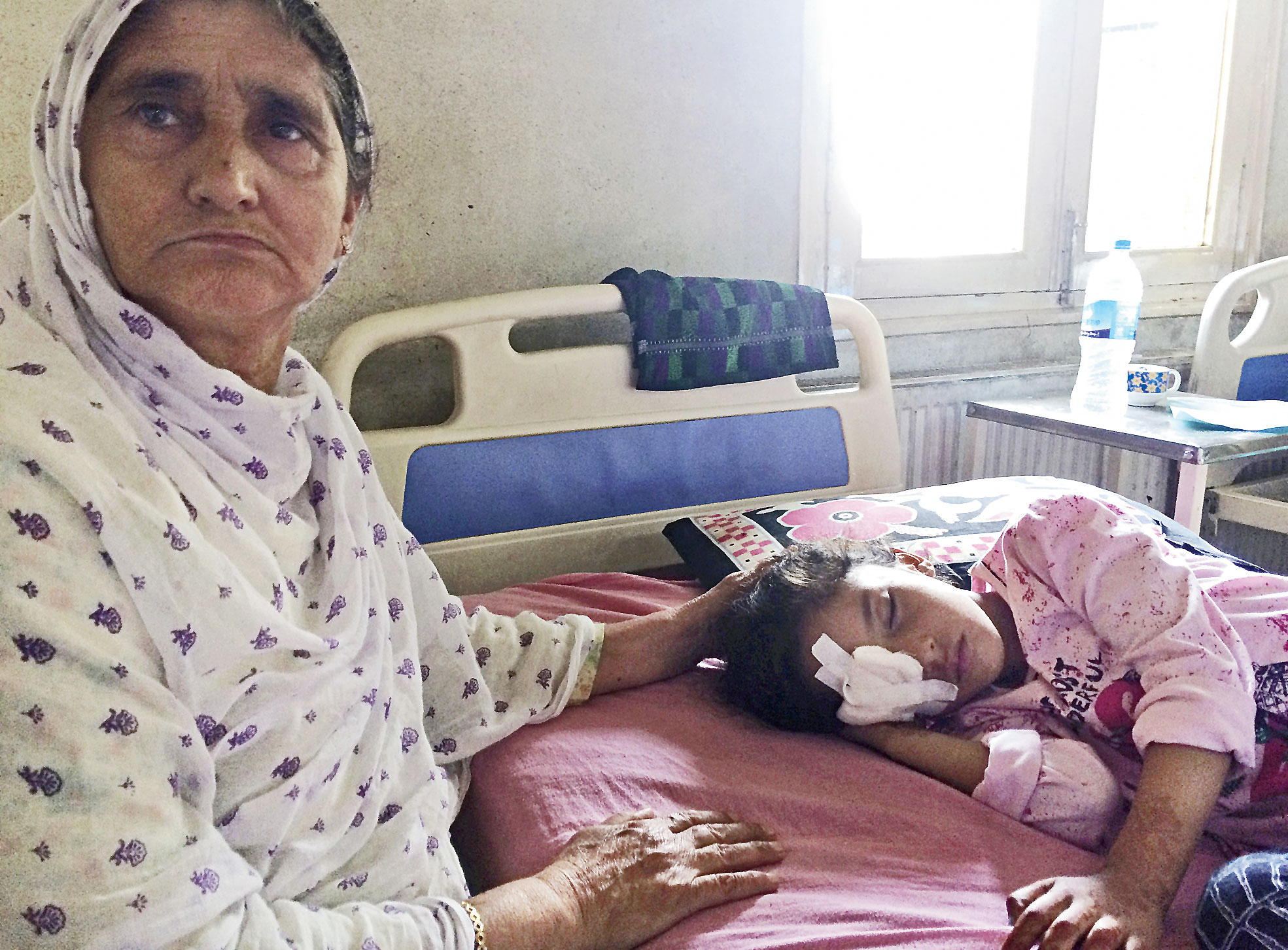 An August 13 picture shows grandmother Sara Ali attending to six year old Muneefa Nazir at a hospital after she was wounded by a marble shot from a sling allegedly used by soldiers in Srinagar .