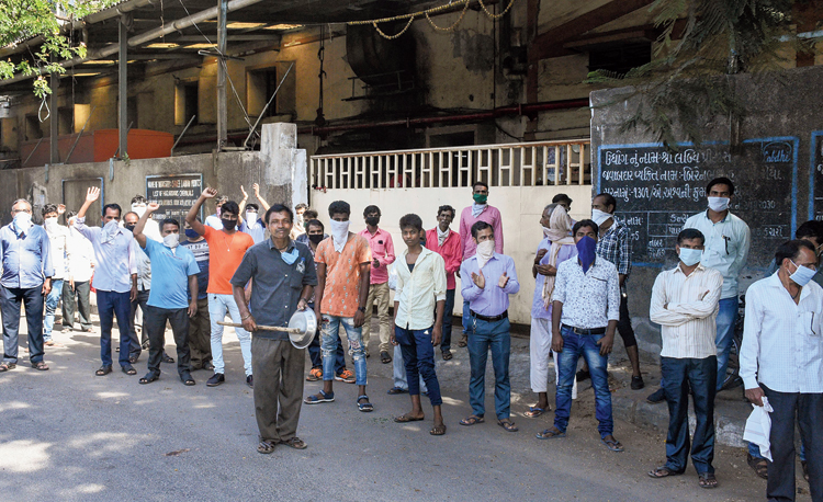 Employees of a dyeing mill protest demanding clearance of pending salary in Surat on Monday.