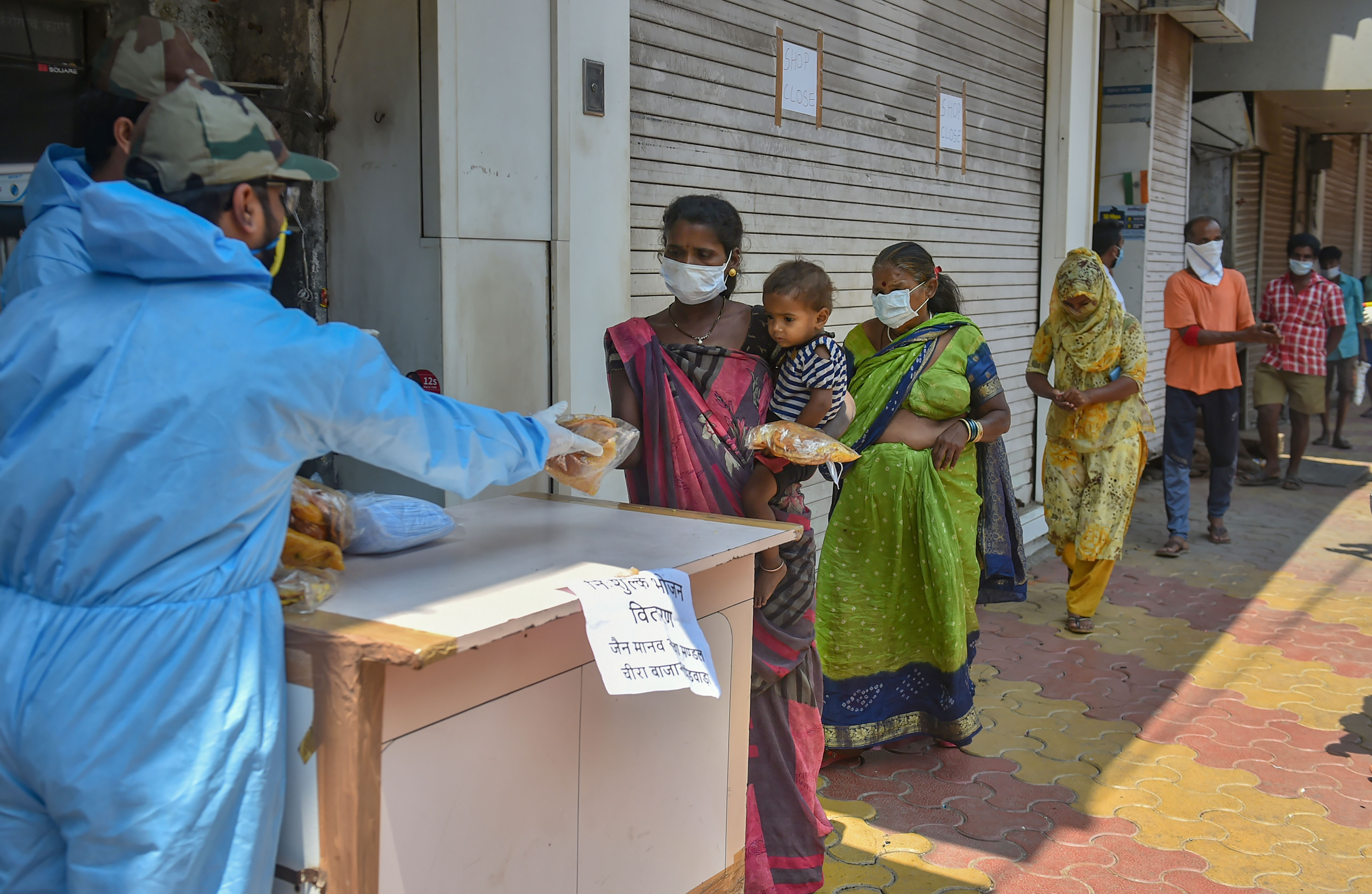 Volunteers distribute packaged food among homeless people during a nationwide lockdown in the wake of the coronavirus pandemic, at Kalbadevi area in Mumbai, Sunday, March 29, 2020