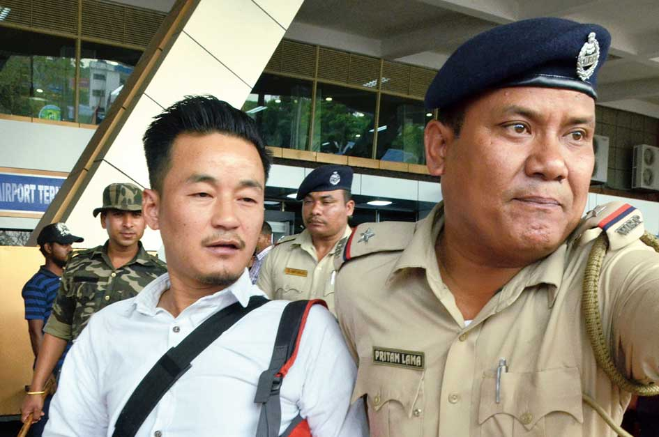 Policemen escort Rohan Rai, leader of the Bimal Gurung faction of the Morcha after their arrival at the Bagdogra airport on Thursday.