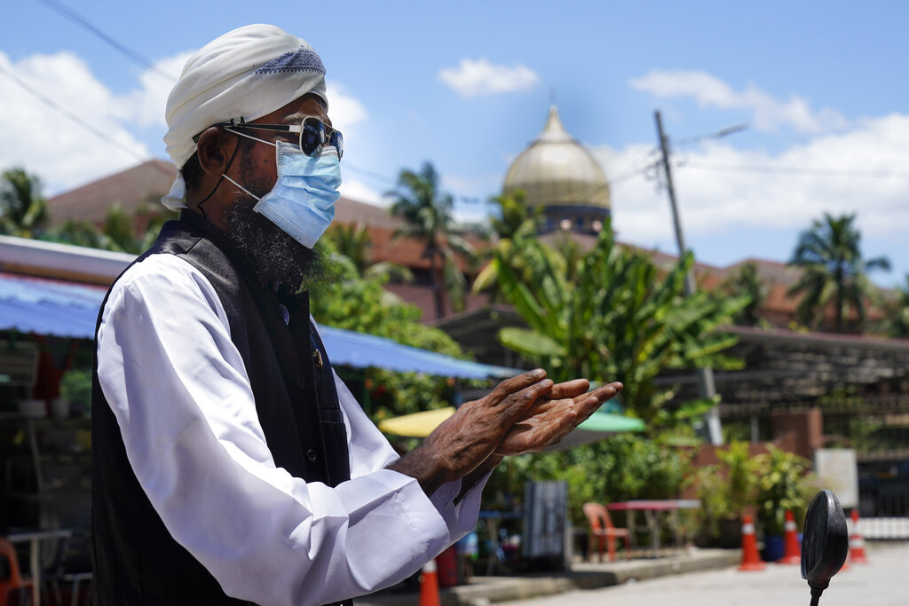 A Muslim man wearing face masks wipes hands with hand-sanitizer as he walks out from Sri Petaling Mosque in Kuala Lumpur, Malaysia.