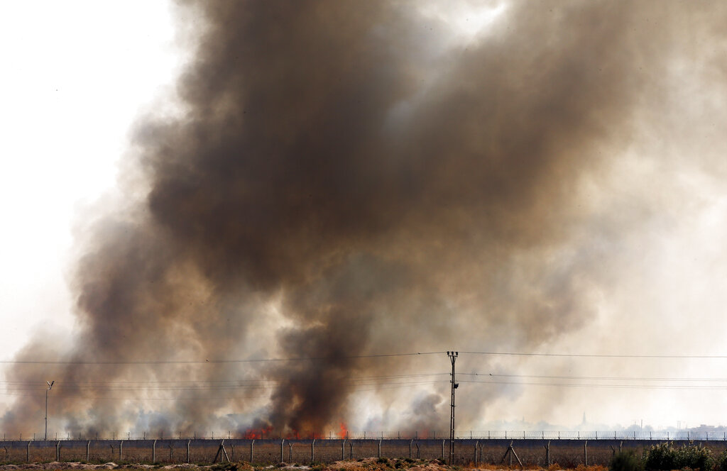 In this photo taken from the Turkish side of the border between Turkey and Syria, in Akcakale, Sanliurfa province, southeastern Turkey, smoke billows from fires on targets in Tel Abyad, Syria, caused by bombardment by Turkish forces on Sunday, October 13, 2019