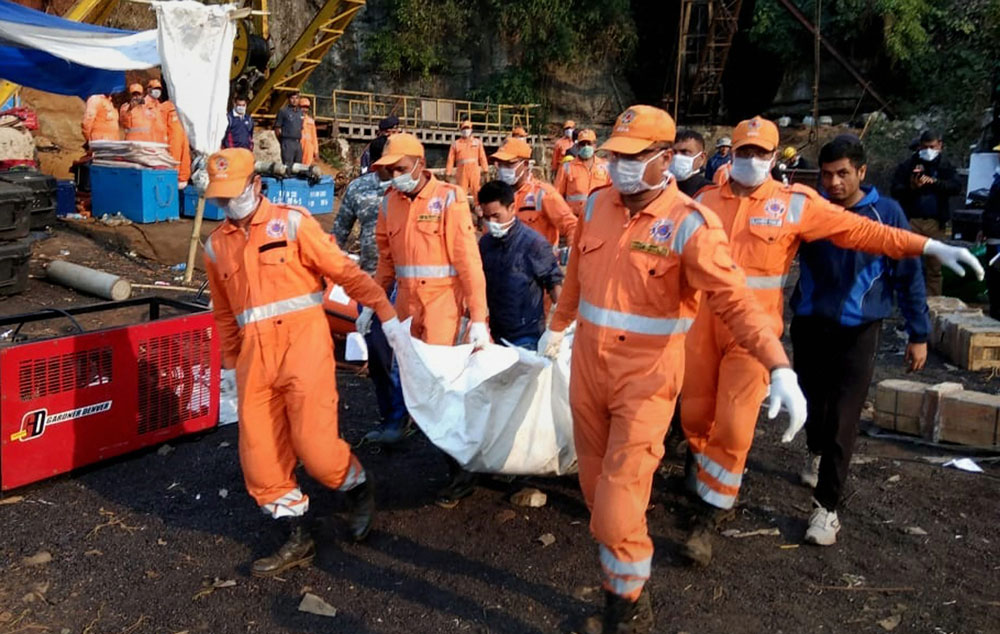 NDRF and Indian Naval personnel carry an unidentified body of a trapped miner during a joint operation in Ksan area of East Jaintia Hills, Thursday, January 24, 2019.