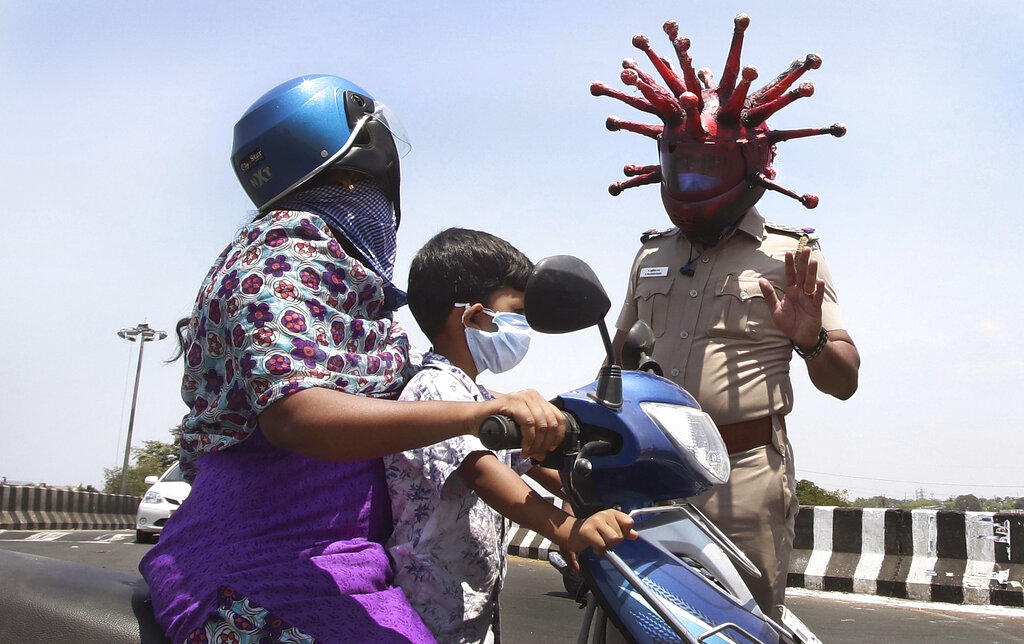 Police officer Rajesh Babu wears a helmet representing the coronavirus, and requests commuters to stay home during the 21-day countrywide lockdown that began Wednesday in Chennai, India, Saturday, March 28, 2020.