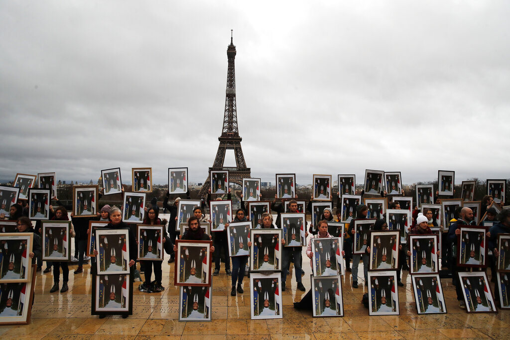 A hundred activists hold portraits of President Emmanuel Macron upside down to urge France to take action during the U.N. COP 25 climate talks in Madrid, during a gathering at Place du Trocadero facing the Eiffel Tower in Paris, Sunday, Dec. 8, 2019.